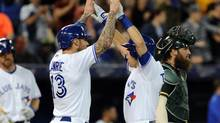 Toronto Blue Jays second baseman Steve Tolleson (right) is greeted at home plate by third baseman Brett Lawrie (13) after driving them both home with a second inning home run against Oakland Athletics at Rogers Centre on May 23, 2014. (Dan Hamilton/USA Today Sports)