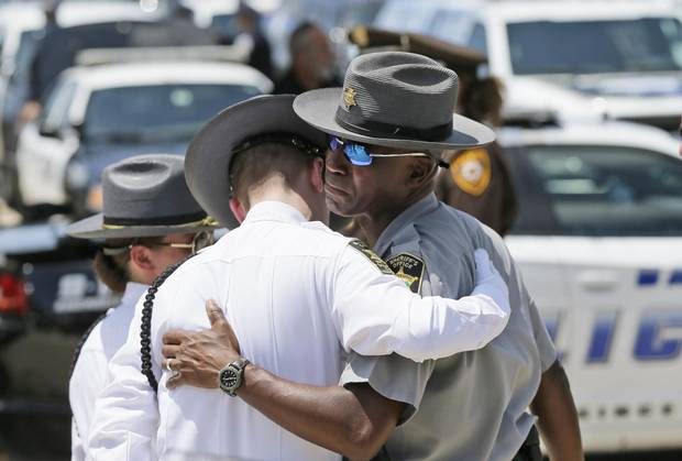 Law enforcement officers comfort each other after the funeral services for Dallas Police Sr. Cpl. Lorne Ahrens at Prestonwood Baptist Church in Plano, Texas.