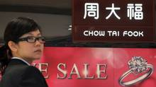 A staff member of a Chow Tai Fook Jewellery store stands by signage in Hong Kong on Nov. 28, 2011. Chow Tai Fook says it is seeking to raise up to $2.8-billion (U.S.) in an IPO that would create a new publicly listed giant in luxury goods. (AARON TAM/AFP/Getty Images)