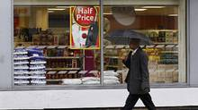 A pedestrian walks past a Tesco store in London April 18, 2012. (SUZANNE PLUNKETT/REUTERS)