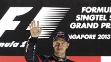 Red Bull Formula One driver Sebastian Vettel of Germany waves on the podium after the Singapore F1 Grand Prix at the Marina Bay street circuit in Singapore on Sept. 22, 2013. (PABLO SANCHEZ/REUTERS)