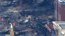 Emergency personnel continue to comb through the debris in the search for remains of the missing in Lac-Mégantic, Que., on July 9, 2013. (Peter Power/The Globe and Mail)