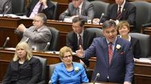Ontario Health Minister Deb Matthews, left, listens as Ontario Finance Minister Charles Sousa delivers the 2014 budget next to Premier Kathleen Wynne at Queen's Park in Toronto on Thursday, May 1, 2014. (Nathan Denette/THE CANADIAN PRESS)