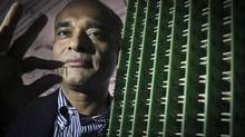 Chet Kanojia, founder and CEO of Aereo Inc., stands next to a server array of antennas as he holds an antenna between his fingers. (Bebeto Matthews/AP)