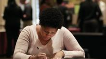 In this Wednesday, Oct. 3, 2012, photo, job hunter Bessie Soley, of Locust Grove, Ga., files out an application at the National Job Fair in Atlanta. (John Bazemore/AP)