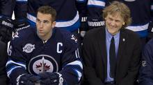 Winnipeg Jets left wing Andrew Ladd (left) and Jets part-owner David Thomson smile as they pose with the rest of the Jets during a team photo prior to