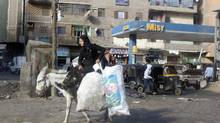 A girl rides a donkey in a shanty town in Cairo Jan. 10, 2013. Political strife in late November and early December set off a rush to convert Egyptian pounds to U.S. dollars, sending the currency to record lows. (ASMAA WAGUIH/REUTERS)