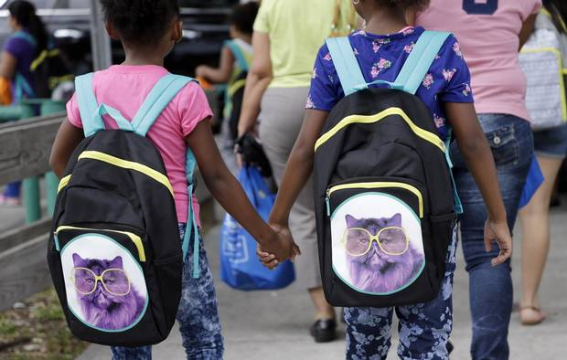 Students hold hands as they walk to school with their new book bags in Miami.