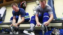 Daniel (right) and Henrik Sedin of the Vancouver Canucks tape their ankles before an ice session (Globe and Mail/Jeff Vinnick)