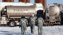 Trican Well Service employees walk towards liquid nitrogen storage tanks at a hydraulic fracturing operation near Bowden, Alta. (Jeff McIntosh For The Globe and Mail)
