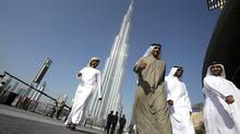 A group of Emiratis walk past the Burj Dubai Tower in Dubai in this file photo. Dubai Group, hit hard by the global financial crisis in 2008 due to excessive leverage and a sharp decline in asset values, has settled with banks that launched legal action against it. (AHMED JADALLAH/REUTERS)