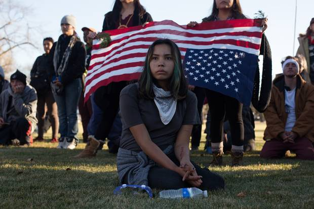 A young woman listens to speakers after a march in Bismarck, N.D., in November. Demonstrators, blocked by riot police, stood and prayed quietly for several hours before peacefully marching away.