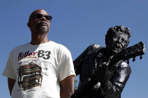 Charles Berry Jr., son of rock 'n' roll legend Chuck Berry, stands with a statue of his late father in Missouri on May 31.