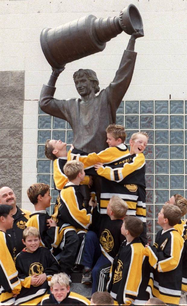 Members of the Northwest Zone Hawks atom hockey team climb onto the Wayne Gretzky statue outside the Skyreach Centre in Edmonton, Saturday, Apr.17, 1999. There has been a steady flow of fans to the statue since Gretzky announced his retirement Friday in New York.
