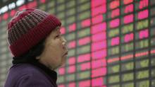 An investor looks at the stock price monitor at a private securities company last month in Shanghai. (Associated Press)