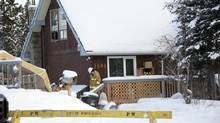 Firefighters examine the scene outside a house in Whitehorse, Jan.30, 2012, where the bodies of five people, including two school-aged children, were found Sunday morning. (VINCE FEDOROFF/THE CANADIAN PRESS)