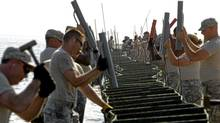 Members of the U.S. Army National Guard's 711 Brigade Support Battalion erect Hesco barriers to potentially stop any oil from damaging Dauphin Island, Alabama Wednesday. Oil spill workers raced against time in the Gulf of Mexico, hoping to take advantage of another day of calm seas in their fight to contain a huge spreading oil slick before it hits the U.S. shoreline. REUTERS/Brian Snyder (BRIAN SNYDER/REUTERS)