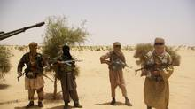 Fighters from Islamist group Ansar Dine stand guard during a hostage handover in the desert outside Timbuktu, Mali, in April. (ASSOCIATED PRESS)