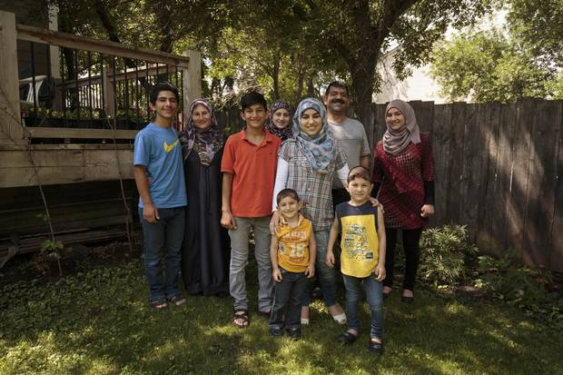Ahmad Daas, his wife Ahlam Dib and their seven children (No. 8 is en route) pose for a family photo outside the home rented for them by their Altona sponsors.