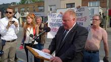 Protester John Furr, right, stands behind Toronto Mayor Rob Ford at a news conference on July 8, 2014. (JILL MAHONEY/THE GLOBE AND MAIL)