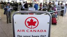 Air Canada travellers wait at the check-in area in Montreal in this file photo (OLIVIER JEAN/REUTERS)