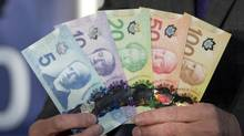 Canada's polymer bank notes are pictured on Nov. 7, 2013. New data from Statistics Canada shows that Canada's top percentile of earners takes home over 10 per cent of the national income. (JONATHAN HAYWARD/THE CANADIAN PRESS)