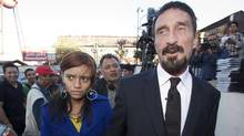 Software company founder John McAfee, right, accompanied by his girlfriend Samantha, leaves after a press conference outside the Supreme Court in Guatemala City, Dec. 4, 2012. (Moises Castillo/AP)