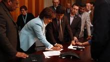 Christy Clark signs a deal with United Truckers association director Meeka Sanghera, left, and Unifor Jerry Dias, middle. (CHAD HIPOLITO/THE GLOBE AND MAIL)
