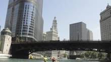 Friends of the Chicago River canoe guides paddle toward the French Rennaissance-style Wrigley Building (centre) and Trump Hotel on the left. (Blair Cosgrove for The Globe and Mail)