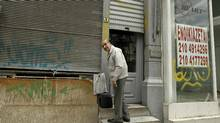 A man prepares to leave his shop next to an empty one with a sign reading 'For Rent' in the port town of Piraeus near Athens. The Greek retail industry is struggling to survive as 30 per cent of small and medium-sized retailers have closed due to austerity measures. (YORGOS KARAHALIS/YORGOS KARAHALIS/REUTERS)