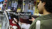 A man reads the latest edition of Vanity Fair with an article on Monica Lewinsky on a news stand in New York May 8, 2014. (EDUARDO MUNOZ/REUTERS)