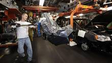 A Chrysler auto worker uses an ergo-arm to load the seats into Chrysler minivans at the Windsor Assembly Plant in Windsor, Ont., Jan. 18, 2011. (REBECCA COOK/Reuters)