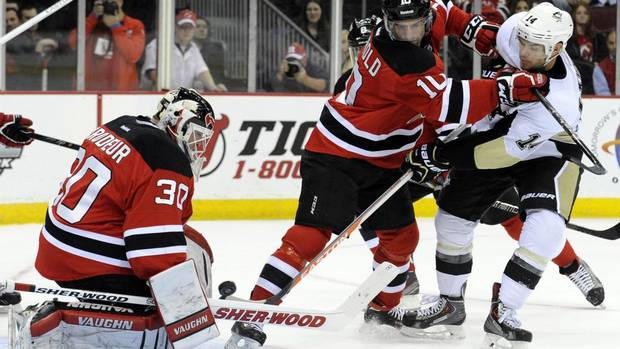 New Jersey Devils goaltender Martin Brodeur, left, makes a save on a shot by Pittsburgh Penguins' Chris Kunitz, right, as he is checked by Devils Peter Harrold during the first period of an NHL hockey game Saturday, Nov. 16, 2013, in Newark, N.J. (BILL KOSTROUN/AP)