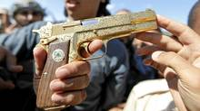 An anti-Gaddafi fighter shows the media what they say was the golden pistol of Moammar Gadhafi, near Sirte October 20, 2011. (THAIER AL-SUDANI/THAIER AL-SUDANI/REUTERS)