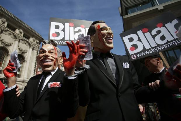 Demonstrators wearing masks depicting Tony Blair and George W. Bush protest in London on July 6, 2016.