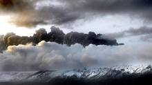 Smoke and steam hangs over the volcano under the Eyjafjallajokull glacier in Iceland, early Thursday April 15, 2010. (BRYNJAR GAUTI/AP Photo/Brynjar Gaudi)