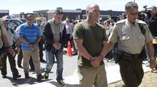 Former Montreal Maine and Atlantic Railway Ltd. employees Thomas Harding, right, Jean Demaitre, centre, and Richard Labrie are escorted by police to appear in court in Lac-Megantic, Que., on Tuesday, May 13, 2014. (Ryan Remiorz/The Canadian Press)