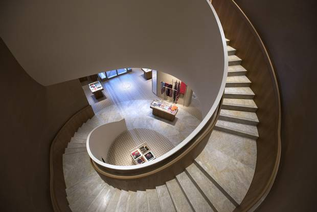 The winding grand stairs, with handrails covered in baby-calf leather, that take shoppers from the main floor to the second level of Hermès's Toronto store.