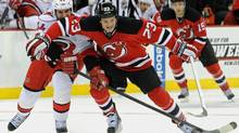 Carolina Hurricanes' Jay Harrison, left, pokes the puck away from New Jersey Devils' David Clarkson during the second period of an NHL hockey game Tuesday, Feb. 12, 2013, in Newark, N.J. (Bill Kostroun/AP)