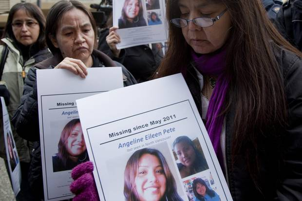 Molly Dixon, right, mother of Angeline Pete, holds up a picture of her missing daughter during a news conference outside the missing and murdered Indigenous women inquiry in Vancouver on Oct. 24, 2011.
