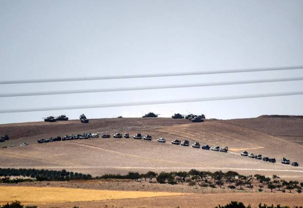 Alleged Syrian opposition fighter trucks and Turkish army tanks are shown massing on the Syria-Turkey border in a photo taken from the Turkish Syrian border city of Karkamis in the southern region of Gaziantep, on Aug. 24, 2016.