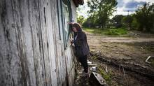 Ronda Kalman looks through the window of her flood-damaged former home earlier this month. (John Lehmann/The Globe and Mail)