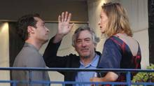 Cannes jury president Robert De Niro waves as he stands on a balcony next to jury members Jude Law and Uma Thurman at the Martinez Hotel in Cannes, on Tuesday. (Reuters)