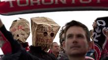Toronto FC fans are loyal, but sometimes embarrassed, too, wearing bags over their heads at the end of last season. (Chris Young/THE CANADIAN PRESS)