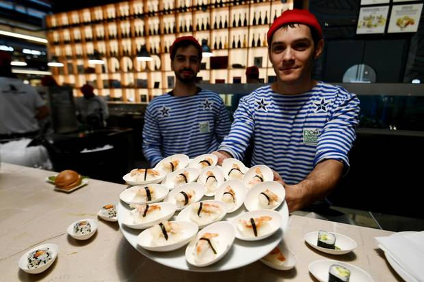 Fishmongers present fish dishes at a stand during a press tour at FICO Eataly World agri-food park in Bologna on November 9, 2017. FICO Eataly World, said to be the world's biggest agri-food park, will open to the public on November 15, 2017.