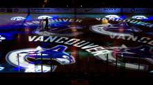 A worker moves a hockey net as Vancouver Canucks team logos are projected on the ice before the team's NHL game against the Detroit Red Wings in Vancouver, B.C., on Thursday February 2, 2012. (DARRYL DYCK/THE CANADIAN PRESS)