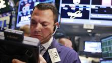 Trader Michael Zicchinolfi works on the floor of the New York Stock Exchange, July 24, 2012. (BRENDAN MCDERMID/REUTERS)