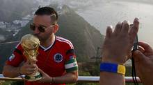 A supporter from Colombia has his picture taken with a replica of the World Cup with Rio de Janeiro in the background from the top of Sugarloaf Mountain ahead of the 2014 World Cup, June 9, 2014. (Reuters)