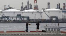 Men fish near an oil refinery in Kawasaki, near Tokyo July 5, 2012. (Toru Hanai/REUTERS)