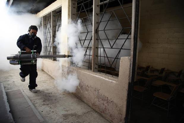A city worker fumigates a public school against mosquitoes in Tegucigalpa, Honduras.